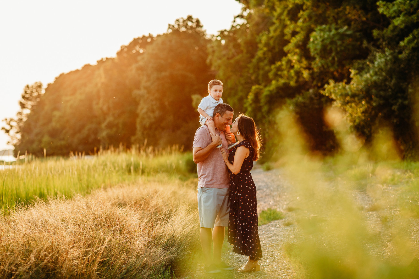 family stands in sunset field with boy on shoulders during family photo session in weymouth ma