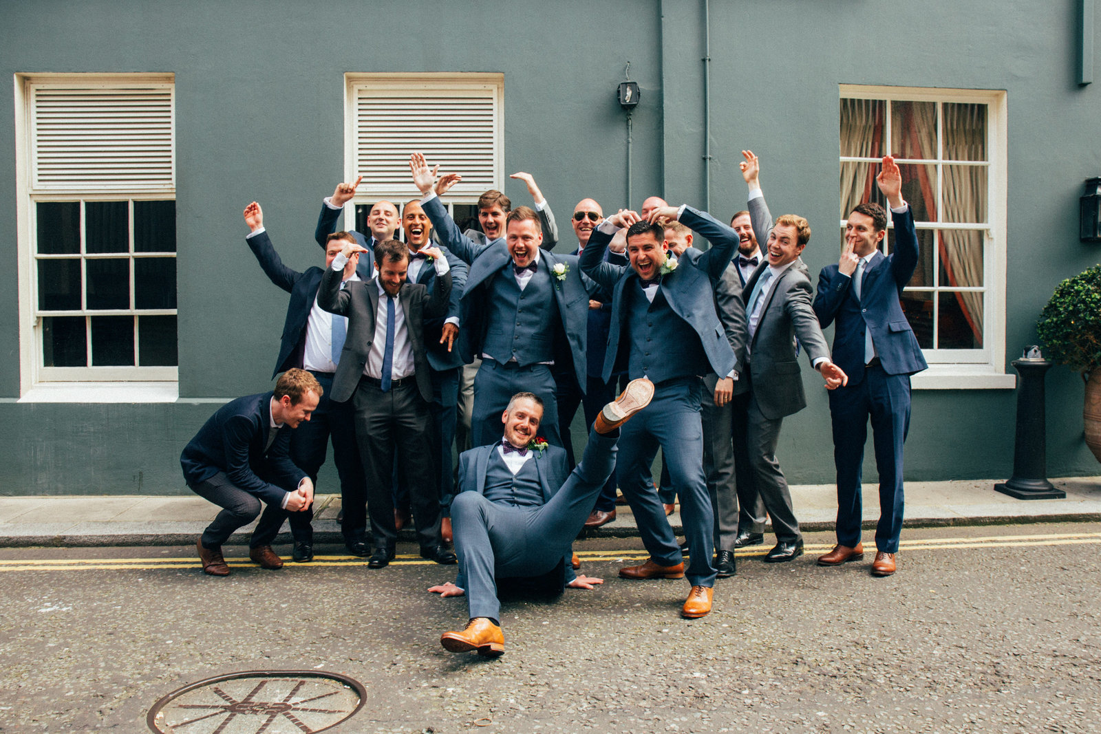 Groom with groomsmen laughing and cheering outside Suffolk wedding venue