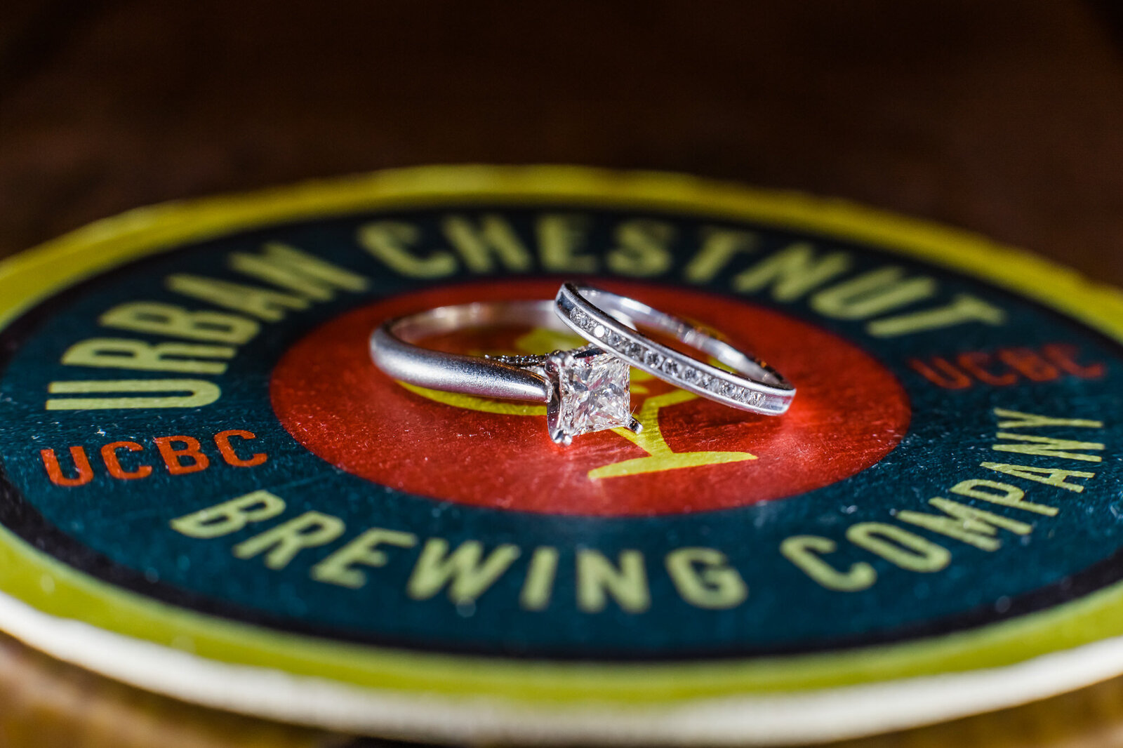 Detail photo of two brides' engagement rings on a local brewery coaster