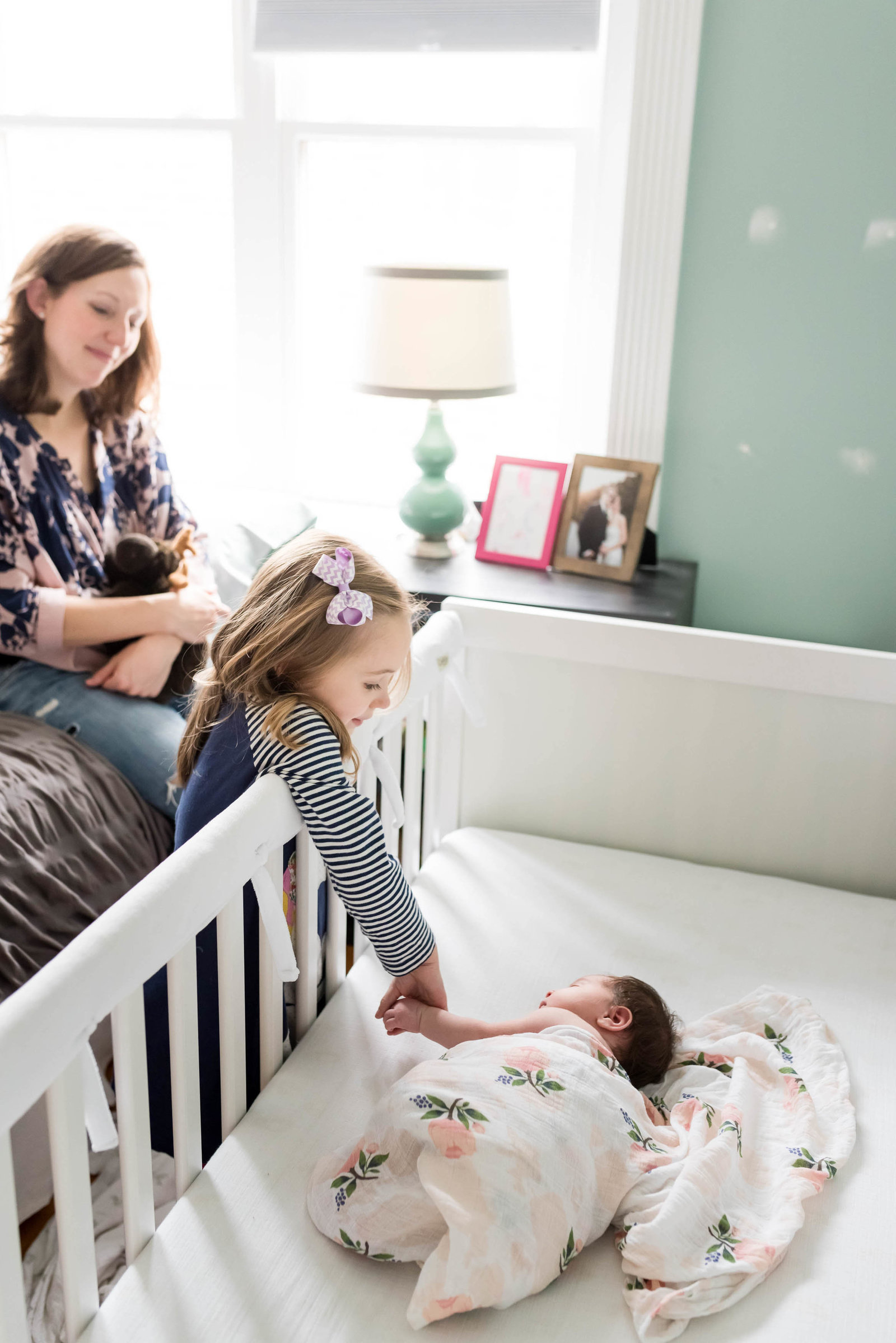 Newborn posed at home on furniture in lifestyle session Boston with sister