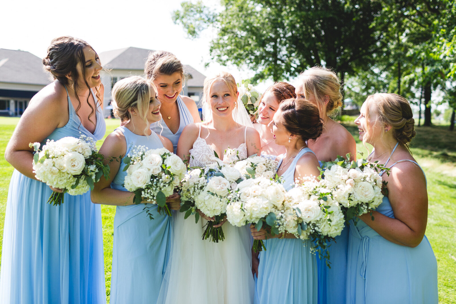 bridal party smiling and laughing in blue with white flowers ohio wedding