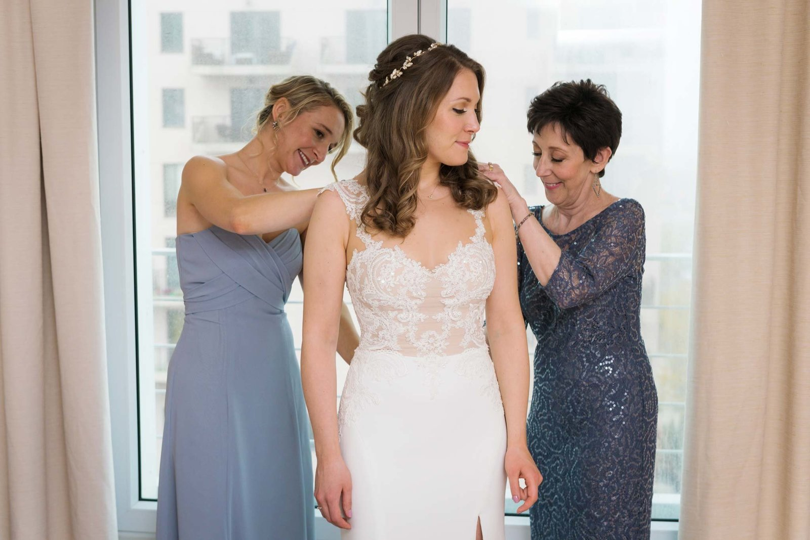 Bride getting dress on with help of bridesmaids at  Allegria Hotel