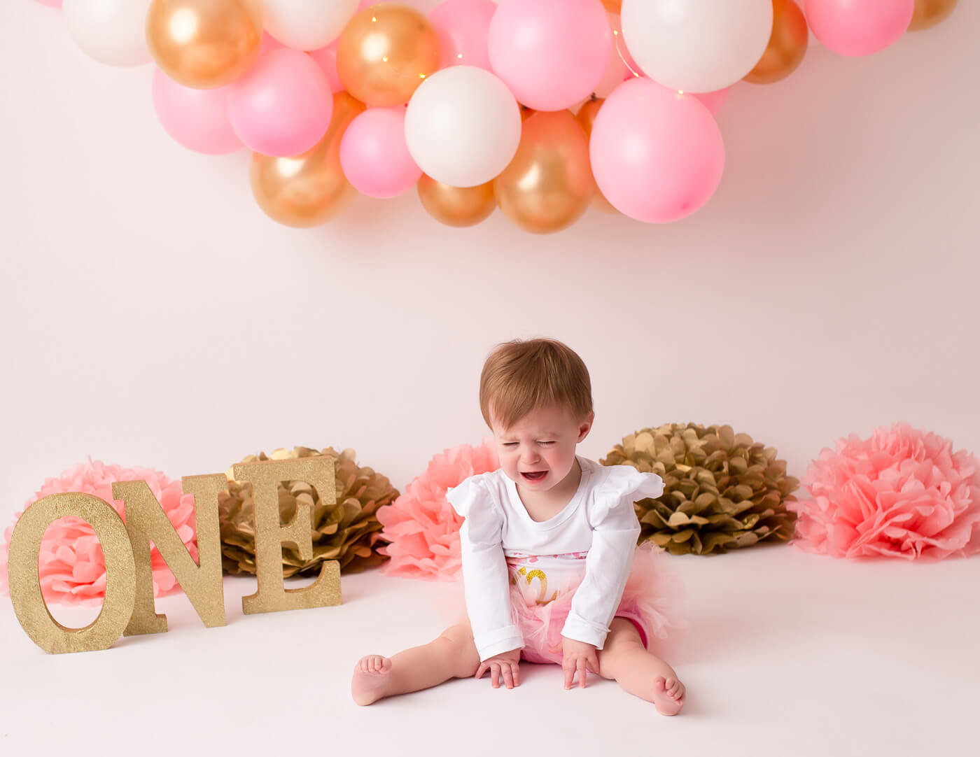 Crying one year old girl at her cake smash in our Rochester, NY studio.