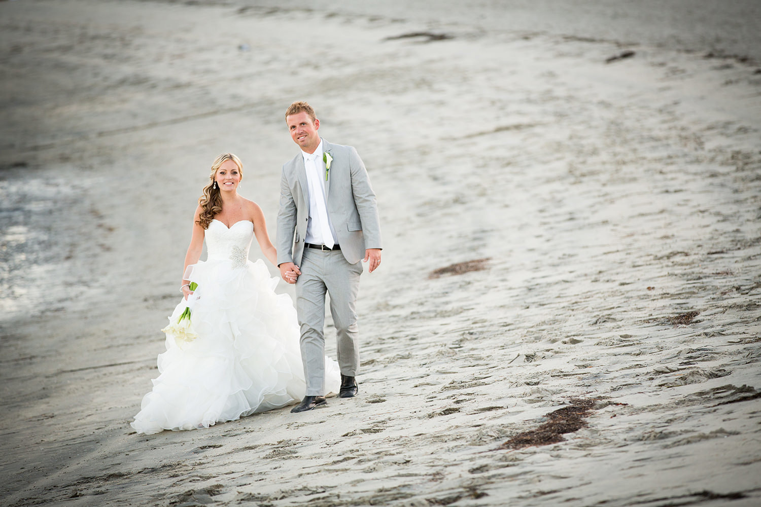 bride and groom in sand walking on beach