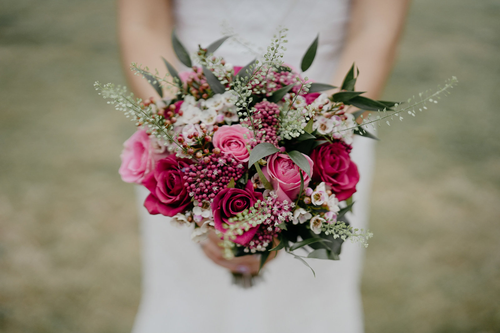 bride holding her beautiful pink, red and green bouquet