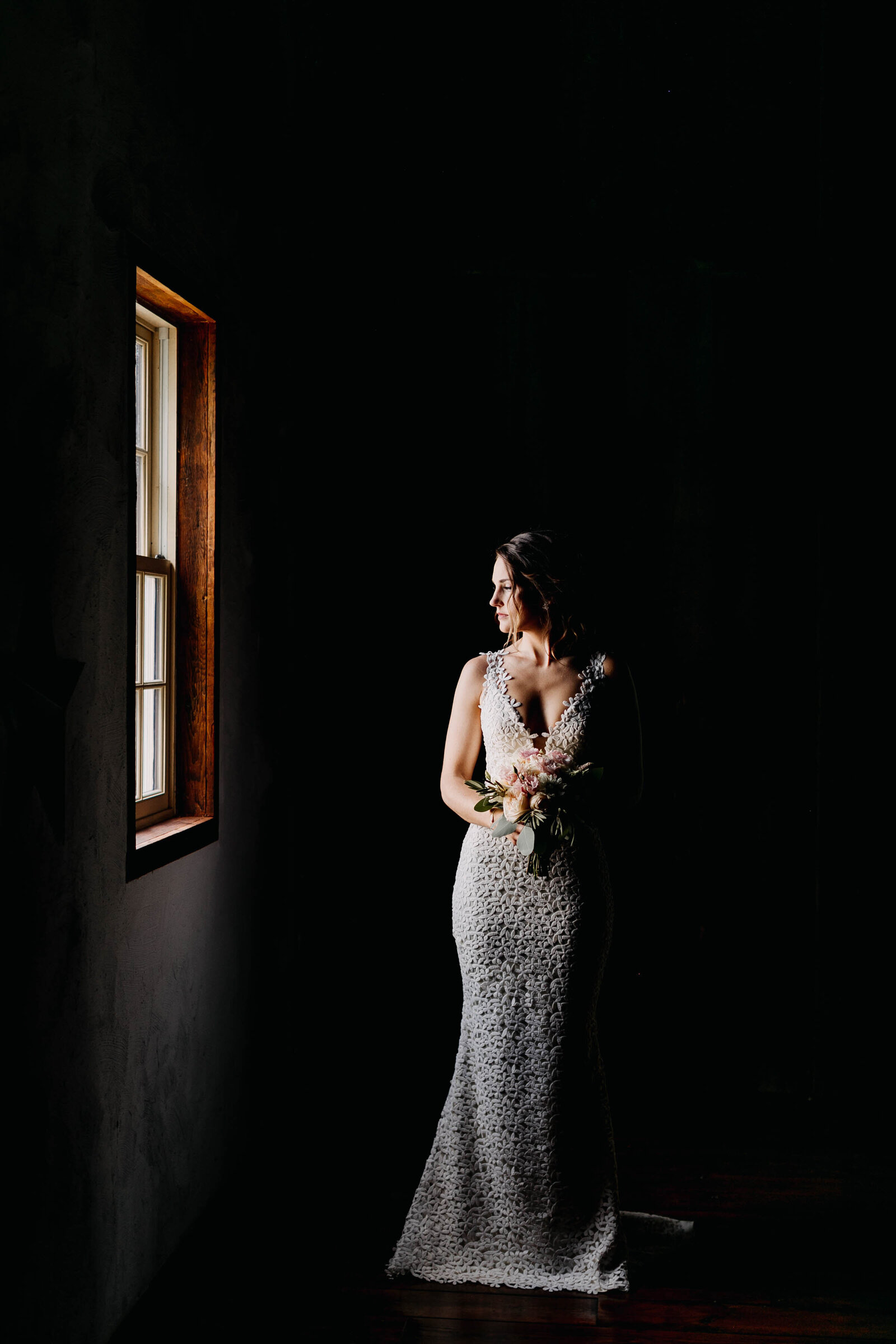 bride looking out window with moody light