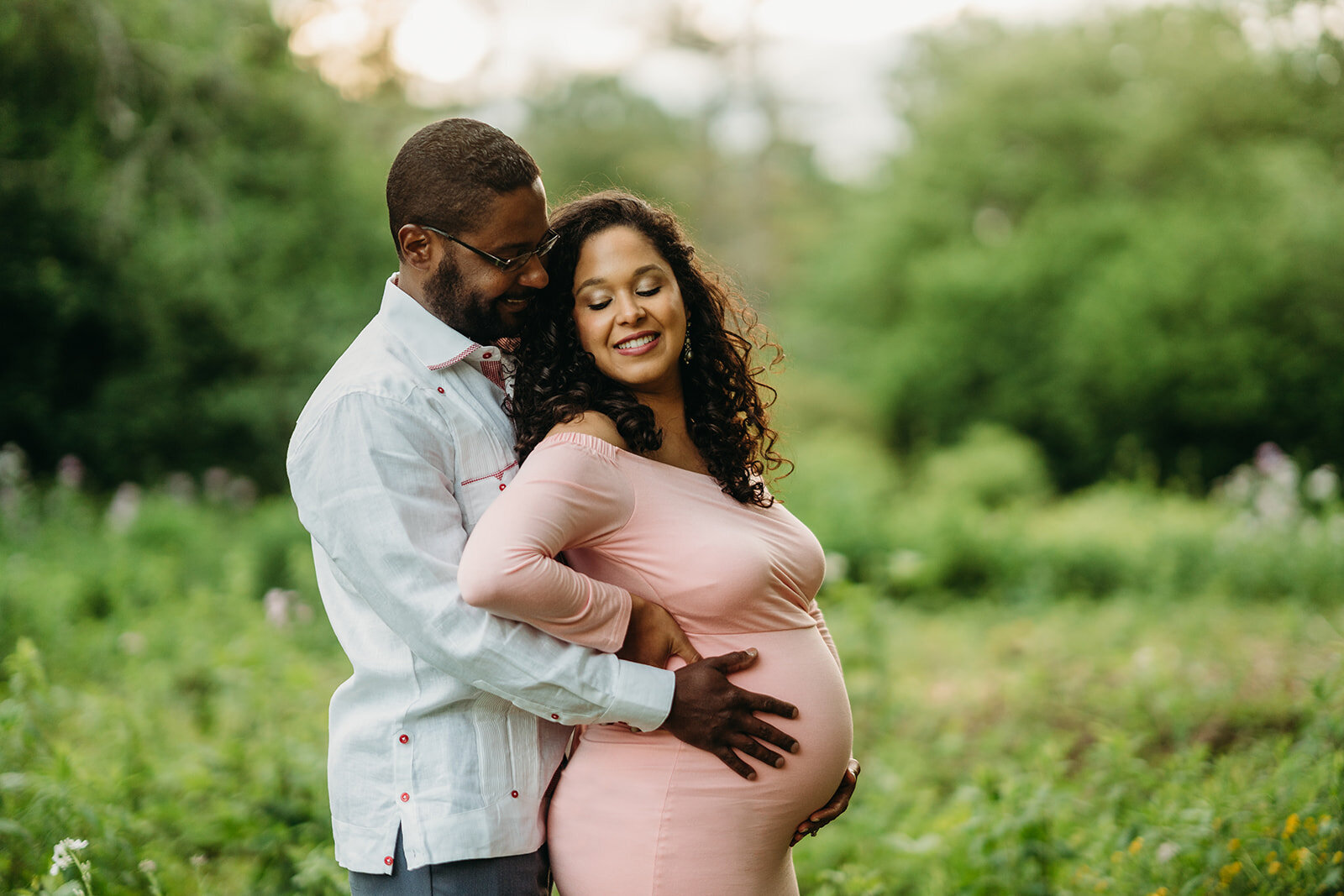 pregnant couple snuggles in spring field in boston