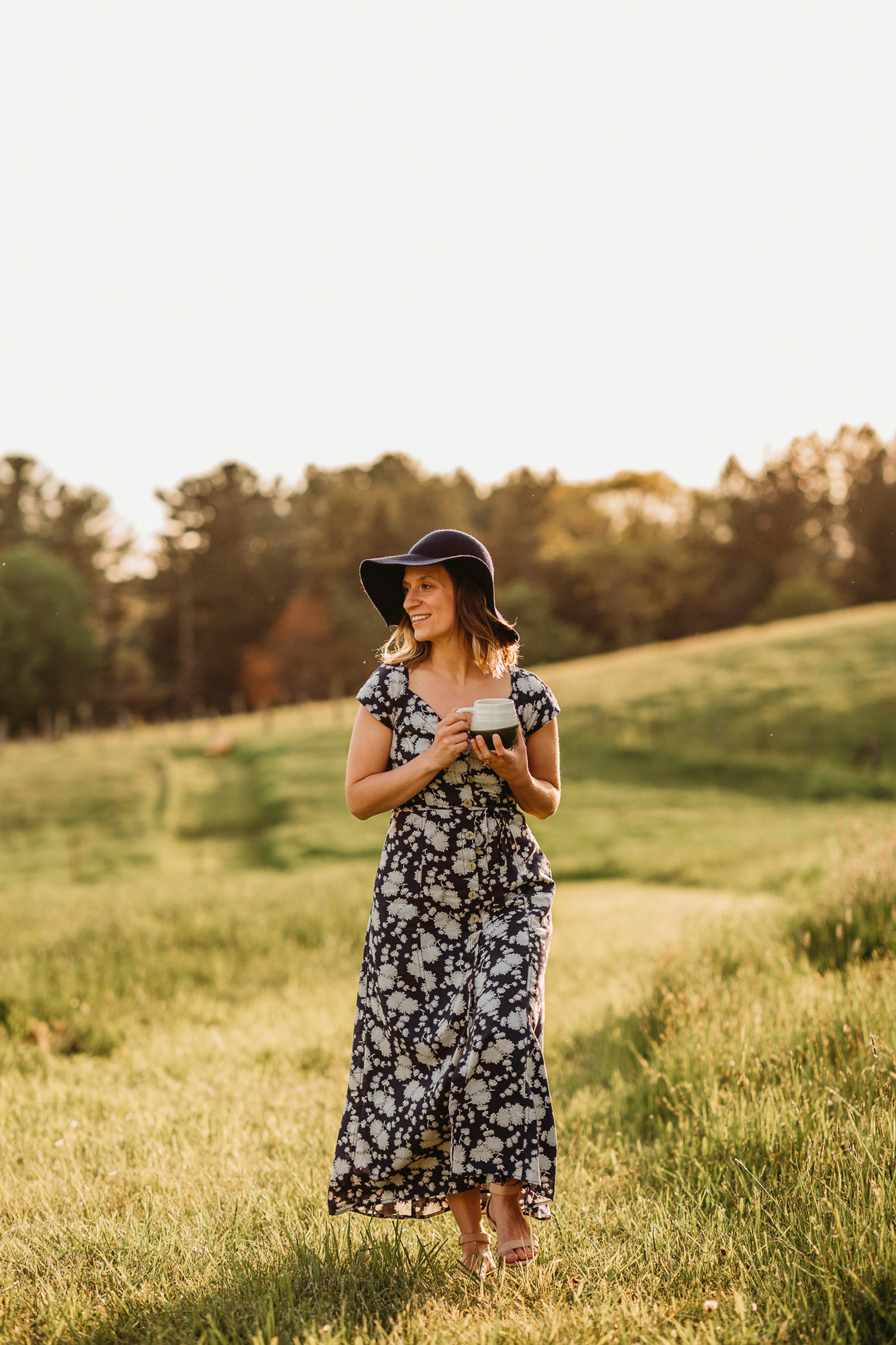 woman in black floral maxi dress stands with pottery mug in field in southborough ma