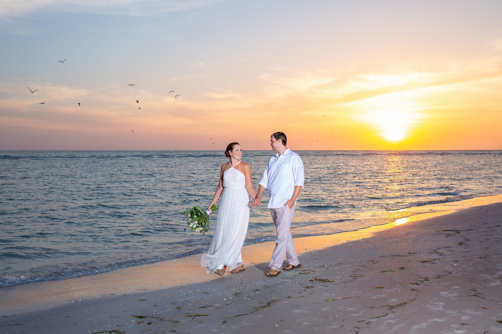 Lido Beach Wedding Photography of bride and groom walking on the beach at sunset