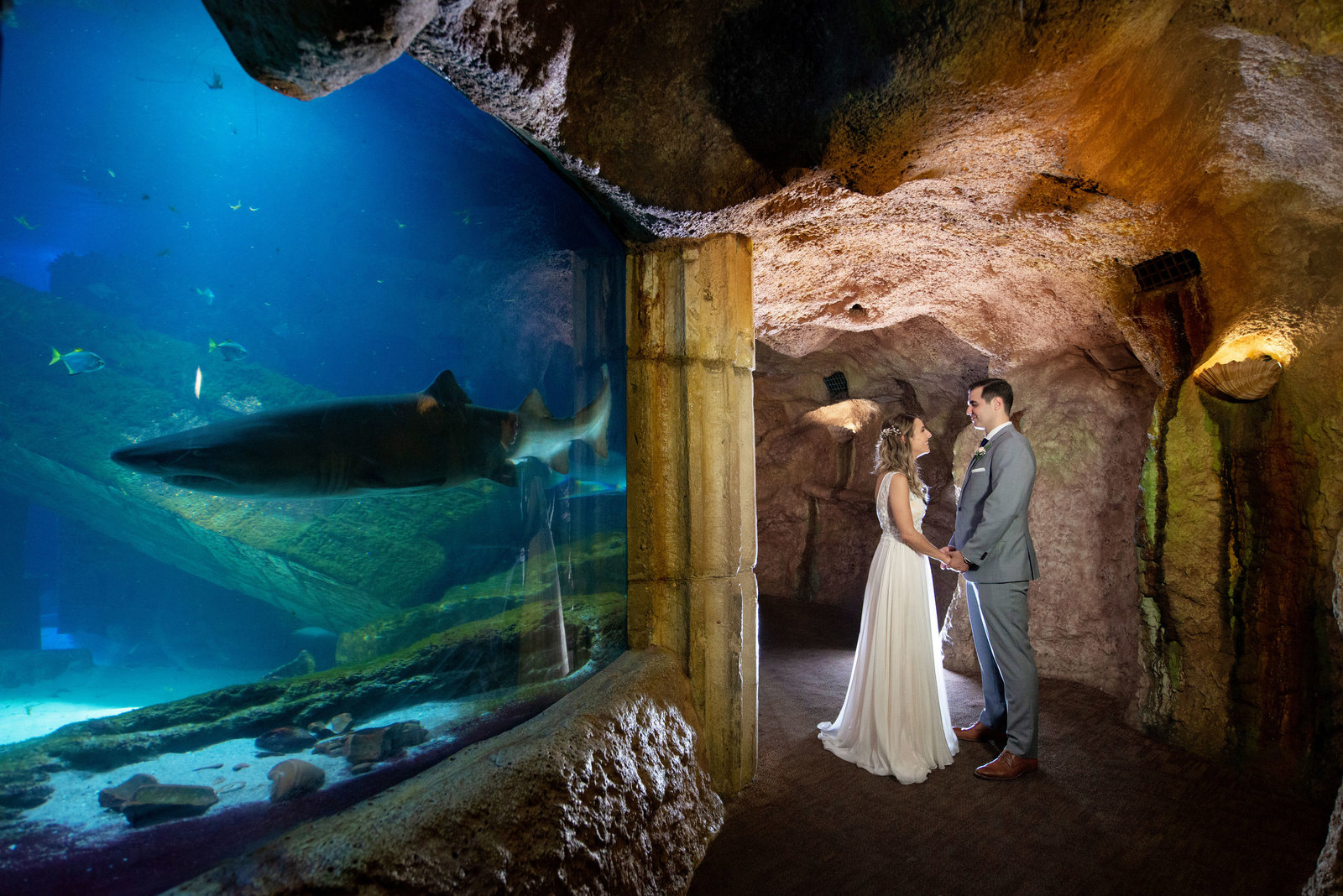 Bride and groom next to sharks at Atlantis Banquet and Events