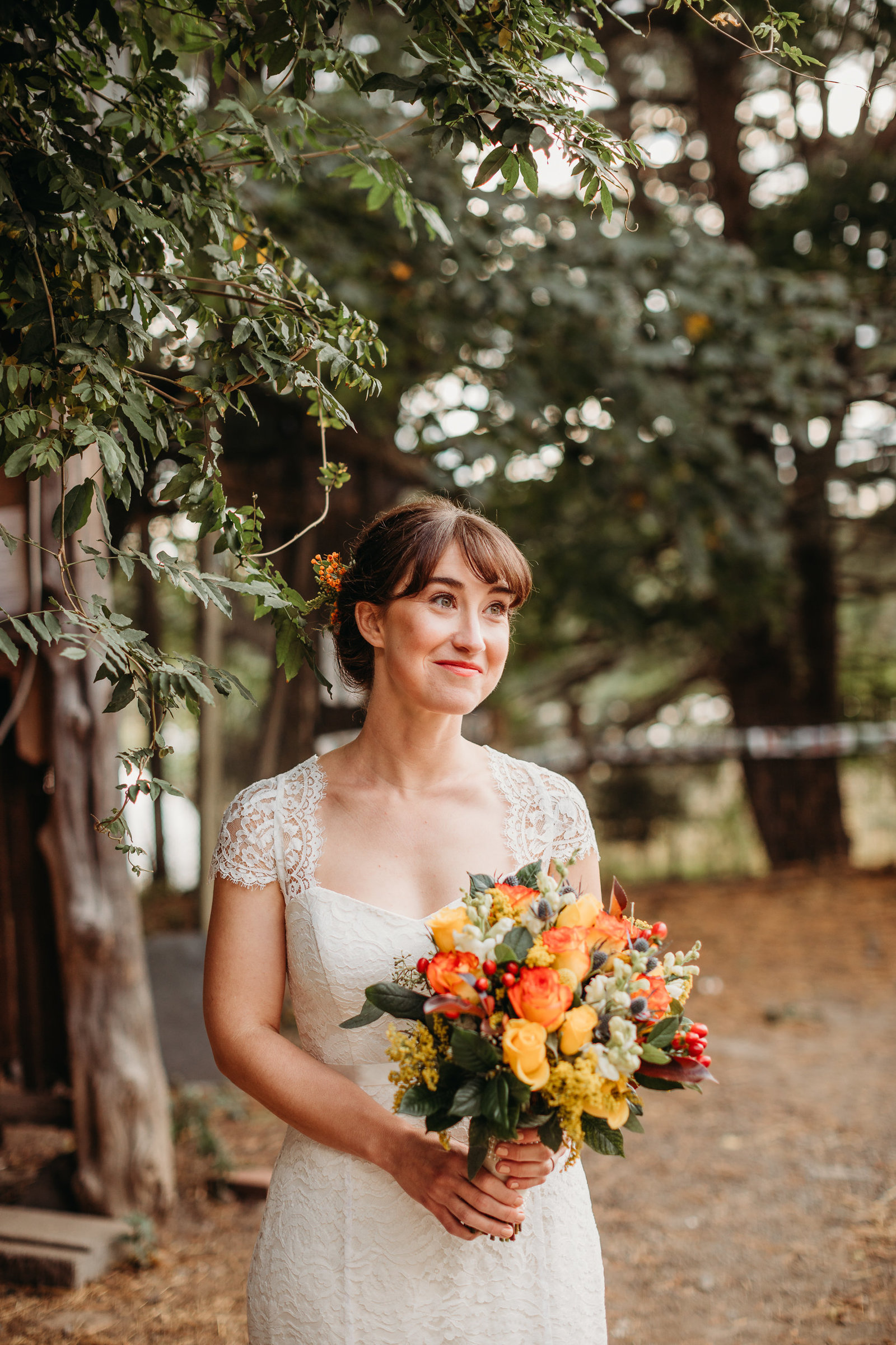 boho bride holds autumn colored bouquet on a farm in massachusetts