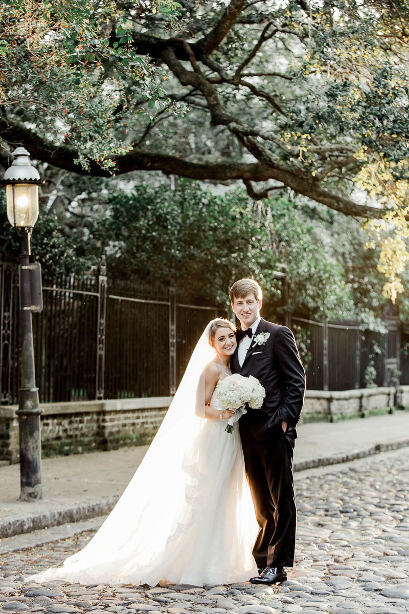 Bride and groom stand on the cobblestones of Washington Square, Charleston, South Carolina. Kate Timbers Photography.