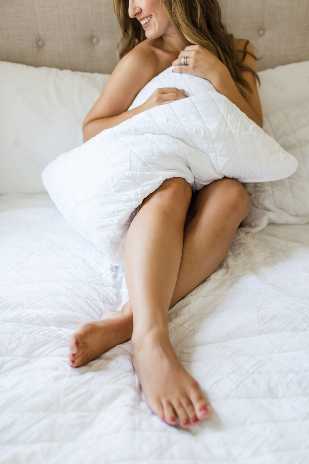 woman holding a pillow during boudoir session
