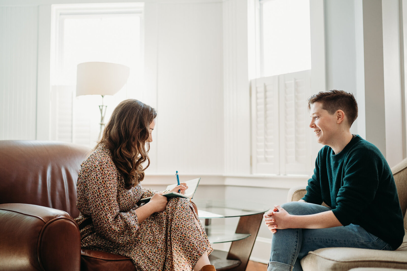 therapist chats with client in an office space during marketing photoshoot