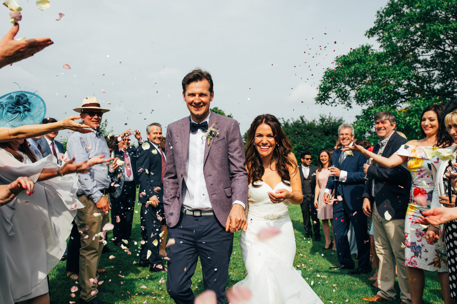 Colourful photograph of newlyweds during a confetti line at their sunny Dove Barn wedding in Sudbury
