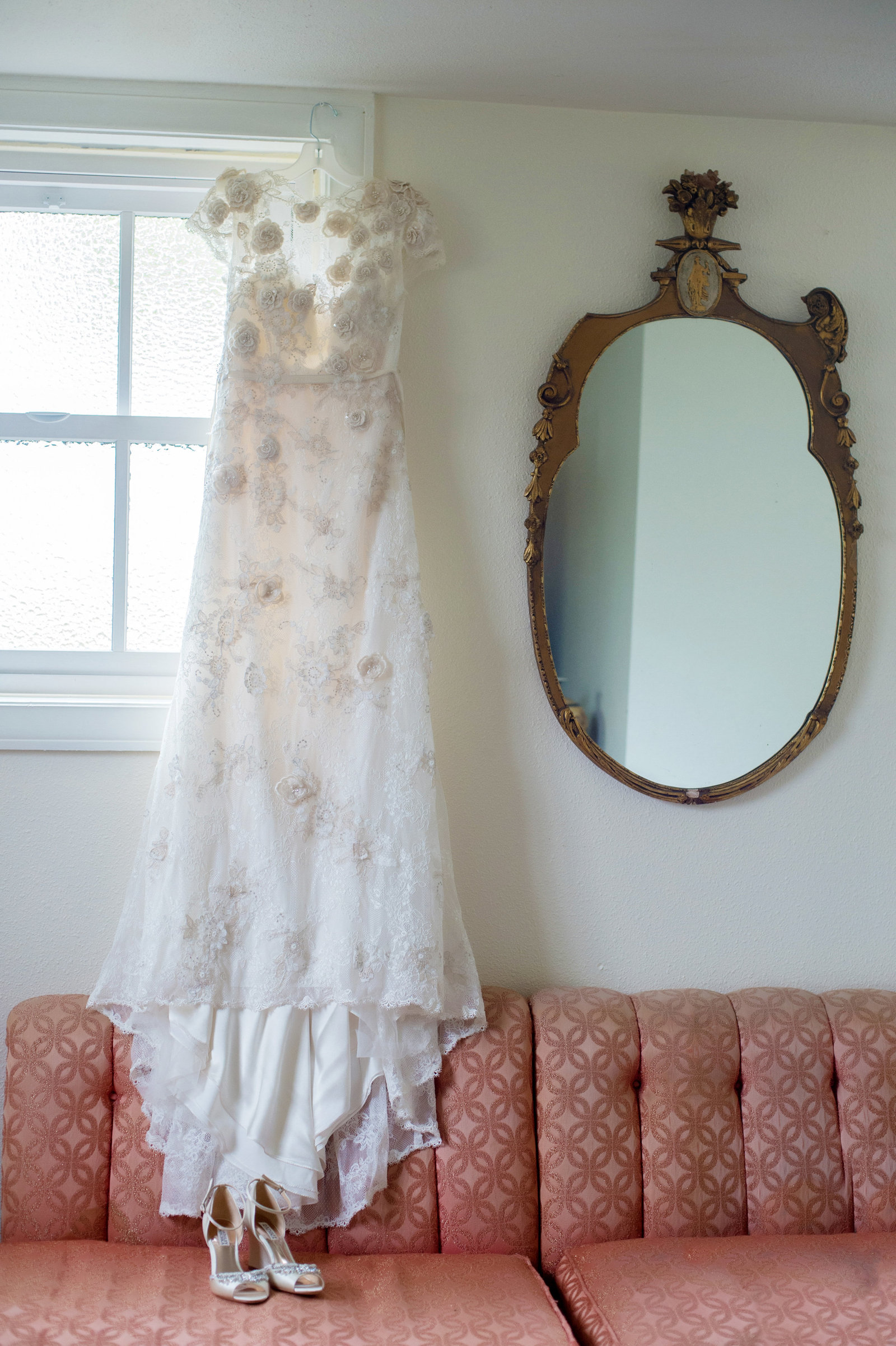 wedding dress hangs beside an antique mirror and pink couch at polaris hall