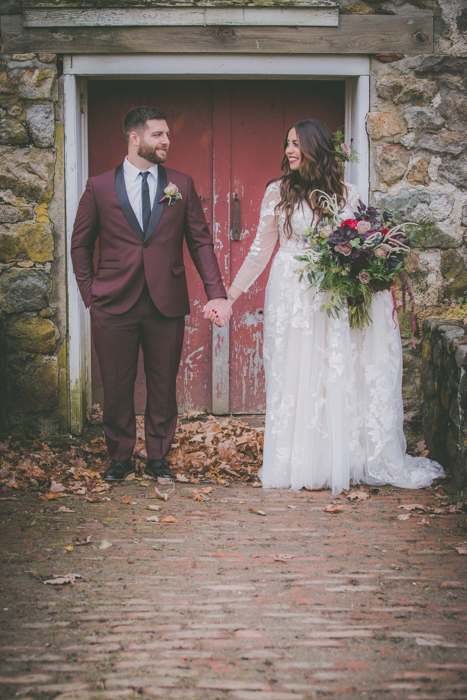 Groom and bride hold hands against a red door.