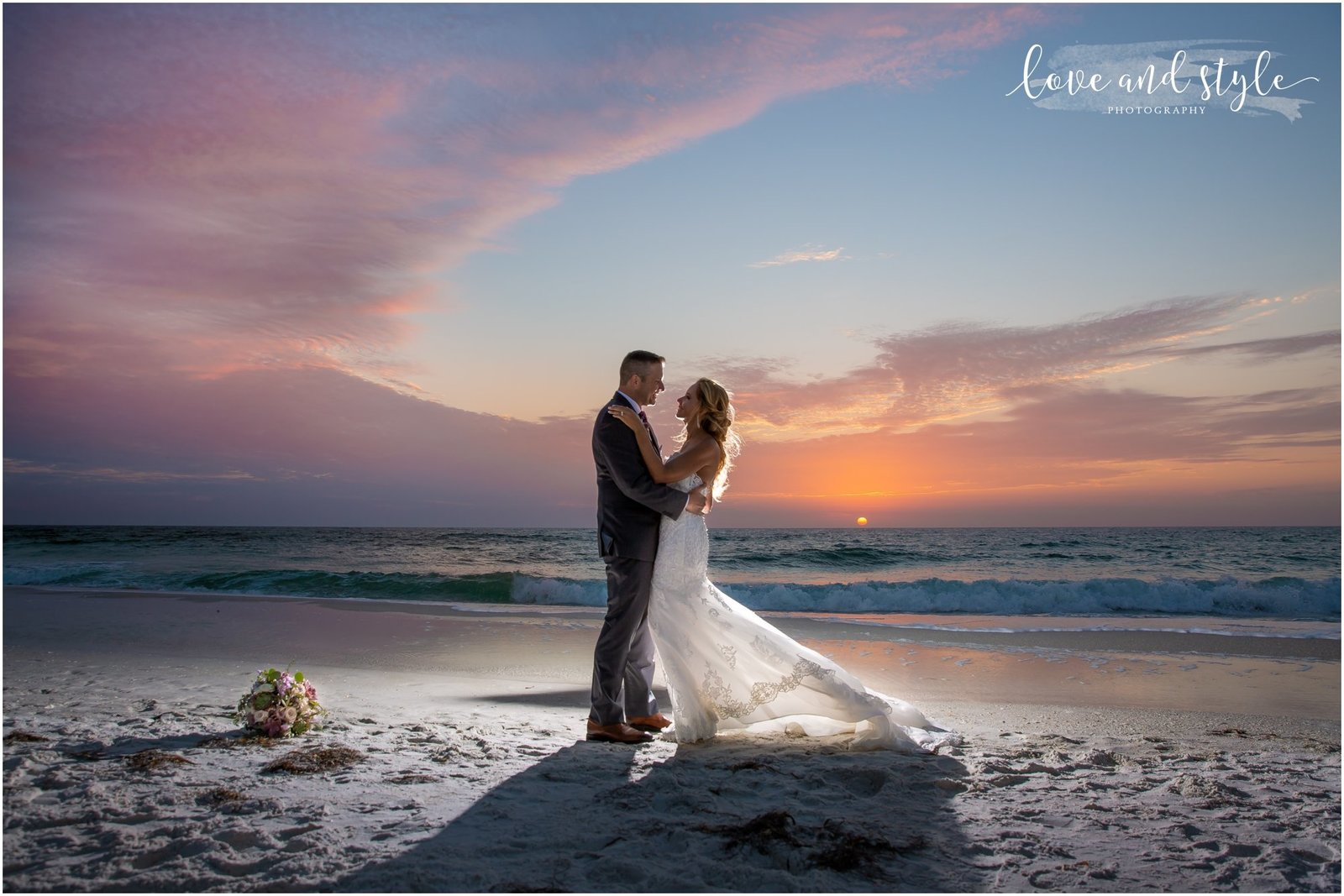 Bride and Groom backlit at Sunset on Holmes Beach in front of The Beach House Restaurant on Anna Maria Island