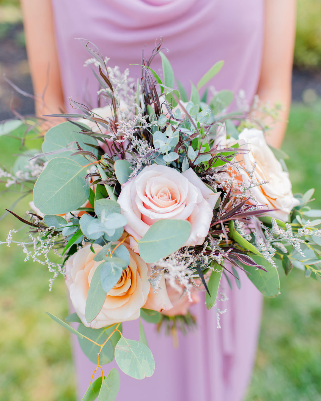 Bridesmaid in mauve dress holding rose bouquet