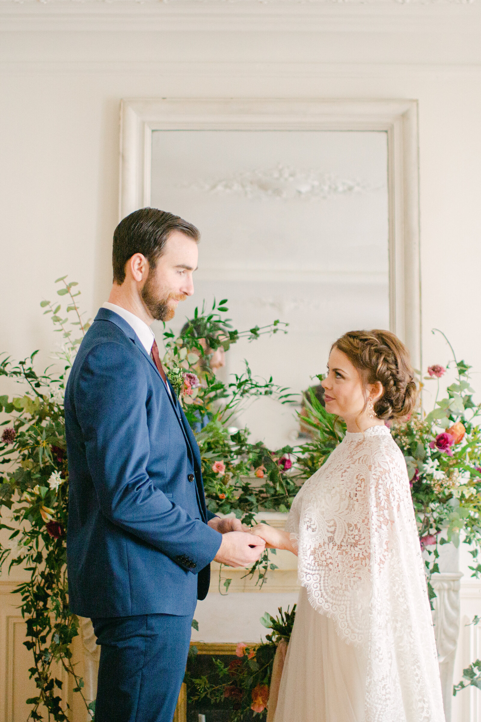bride and groom in front of fireplace mantel in paris apartment exchanging vows