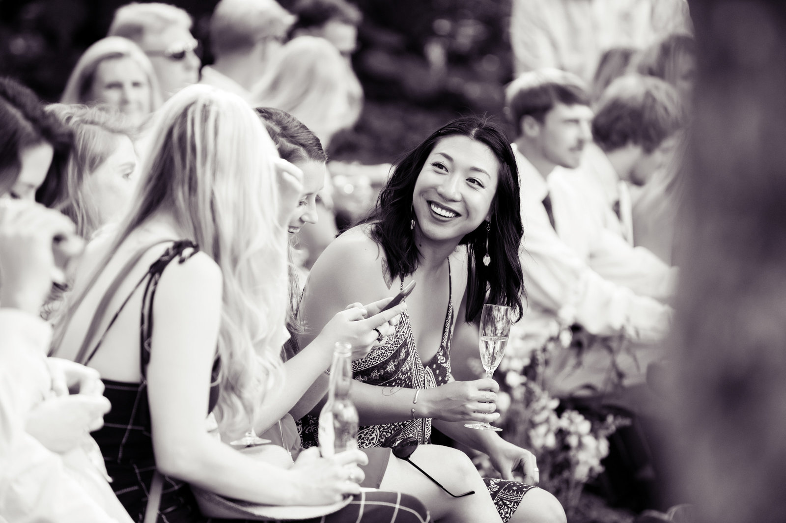 wedding guests laugh as they wait for the ceremony to begin