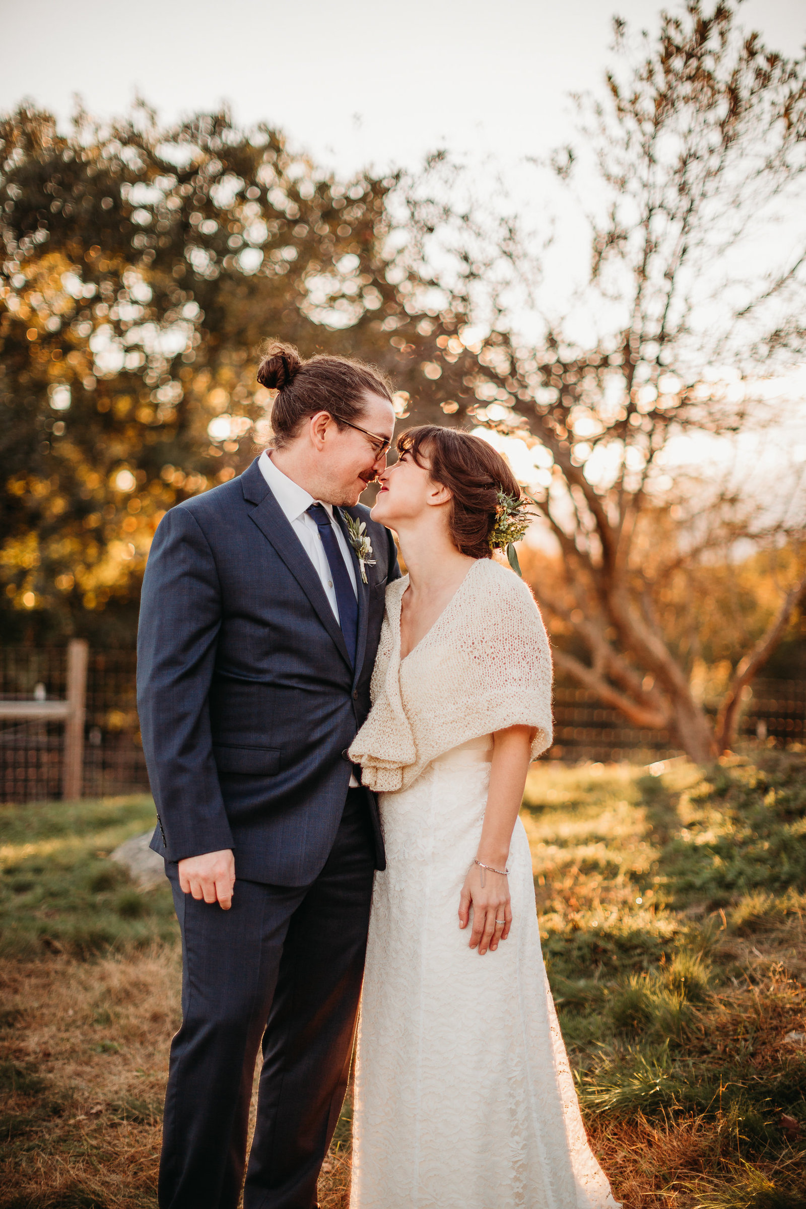 bride and groom go nose to nose during sunset pictures on a farm in massachusetts