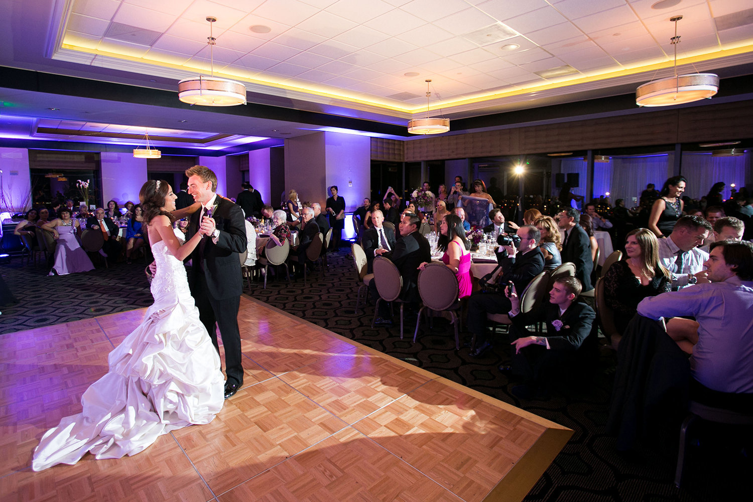 The first dance as a large crowd of wedding guests watch at the University Club on Symphony Tower | Reception Uplighting