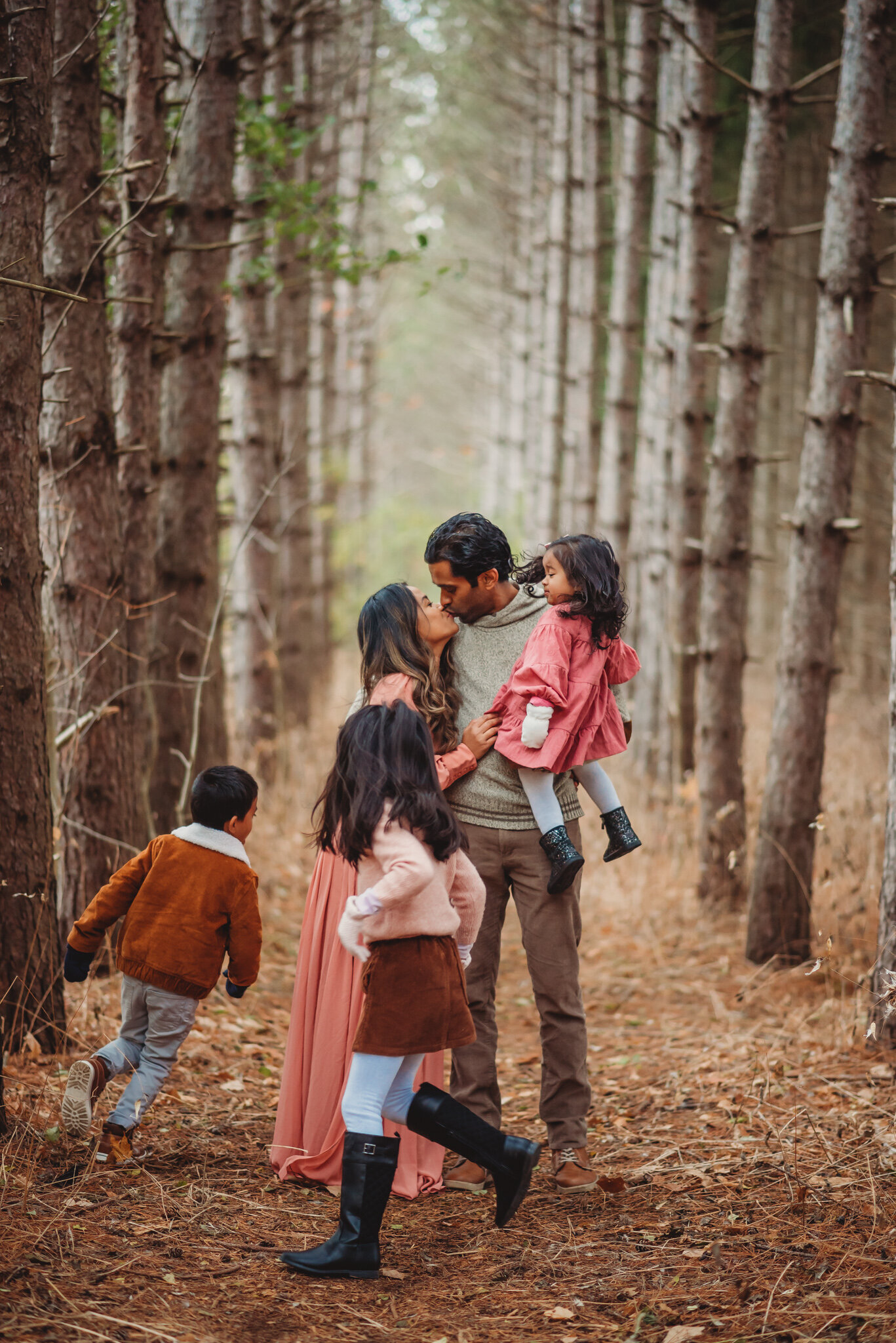 Parents embracing in a tall pine forest in Ajax