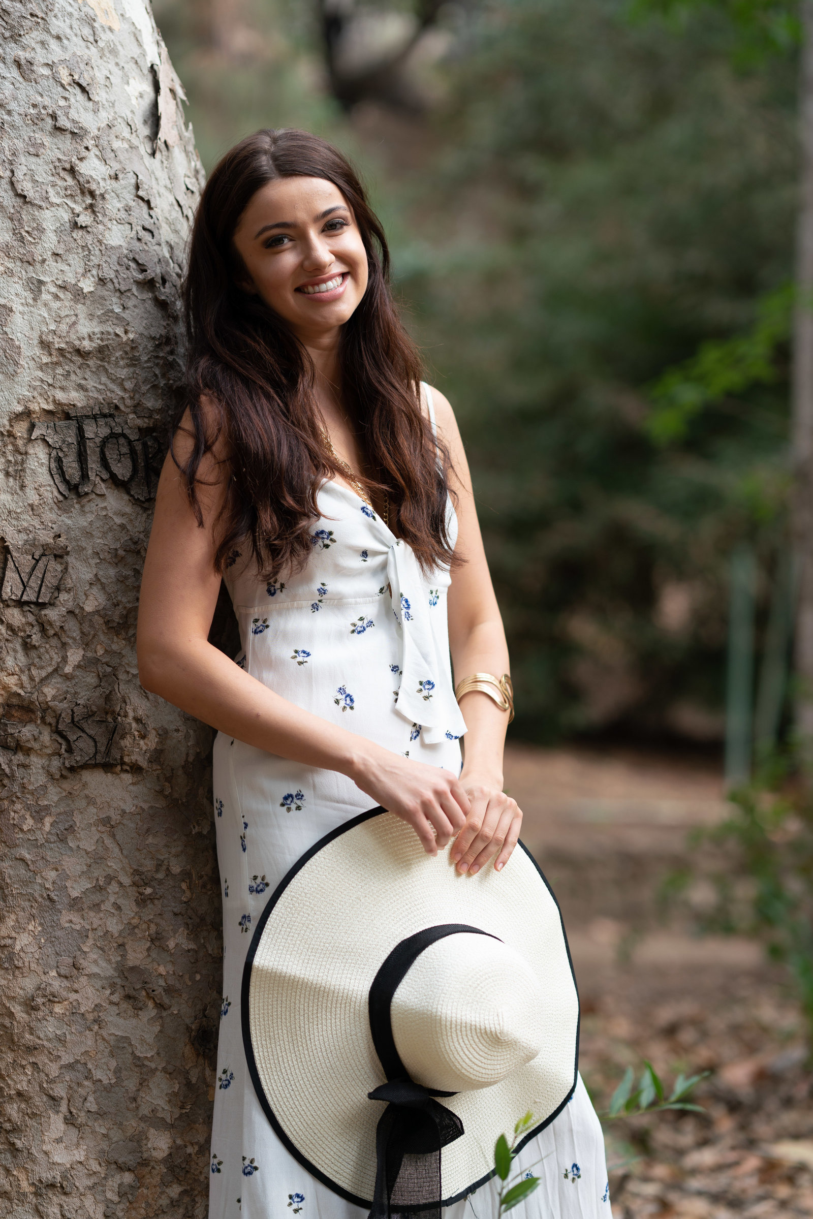 Natural smile model holding white hat leaning against tree