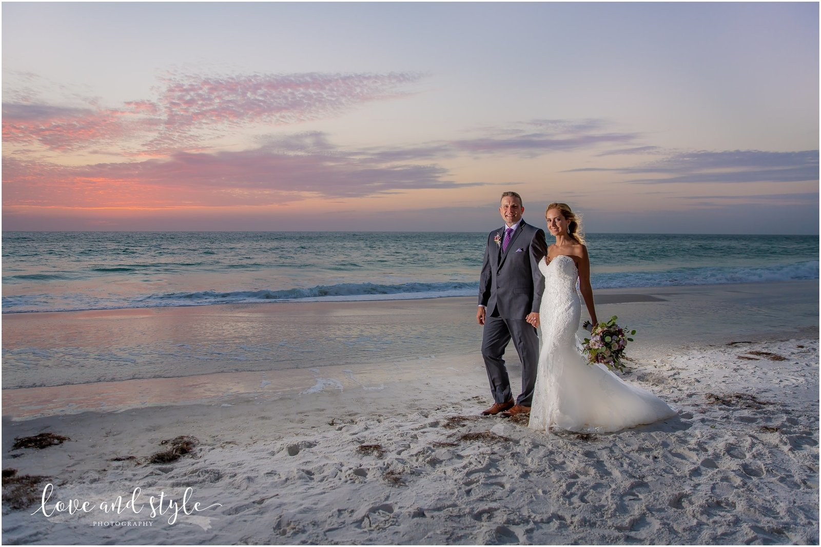 Bride and Groom walking on the beach at sunset in front of The Beach House on Anna Maria Island