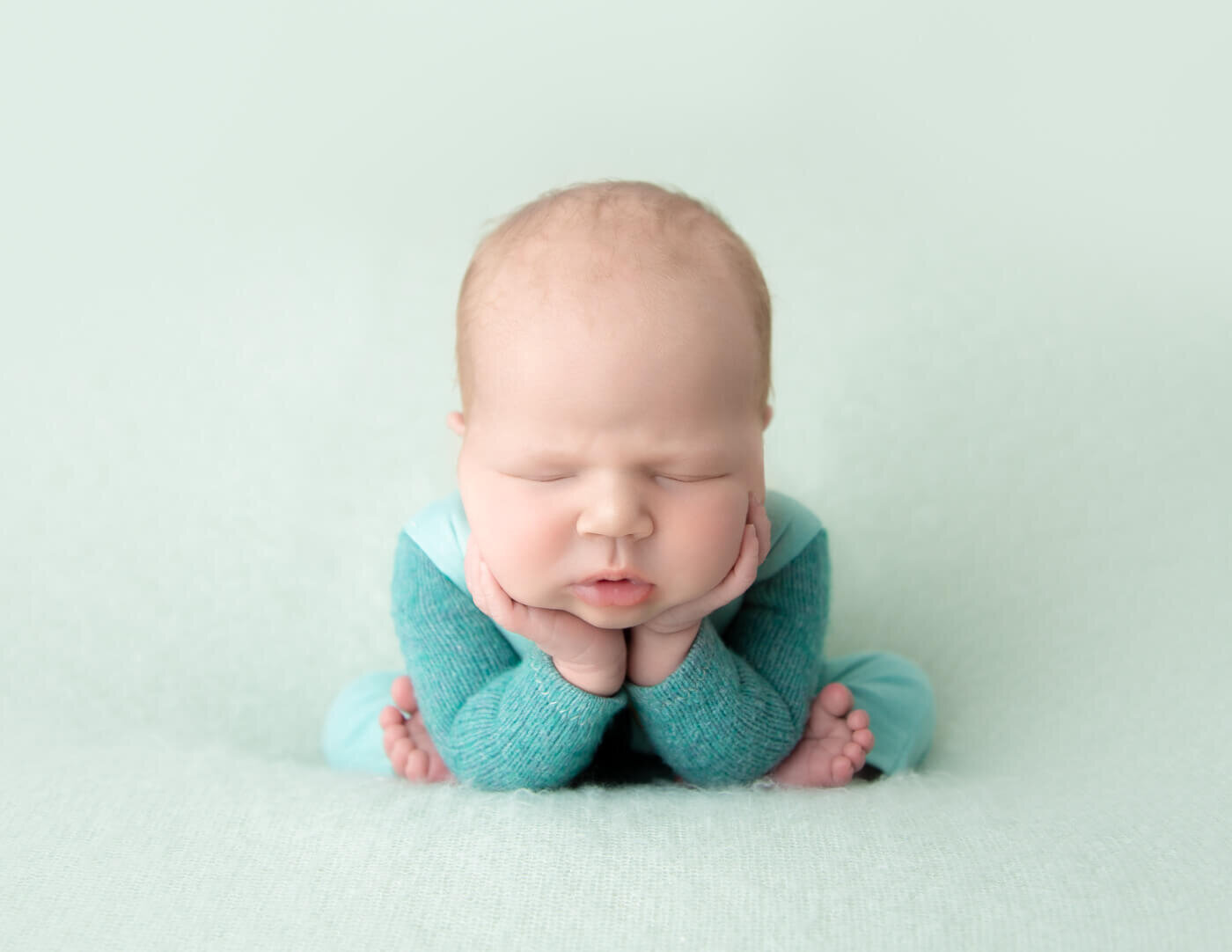 Sweet newborn boy in froggy pose in our Rochester, NY studio.