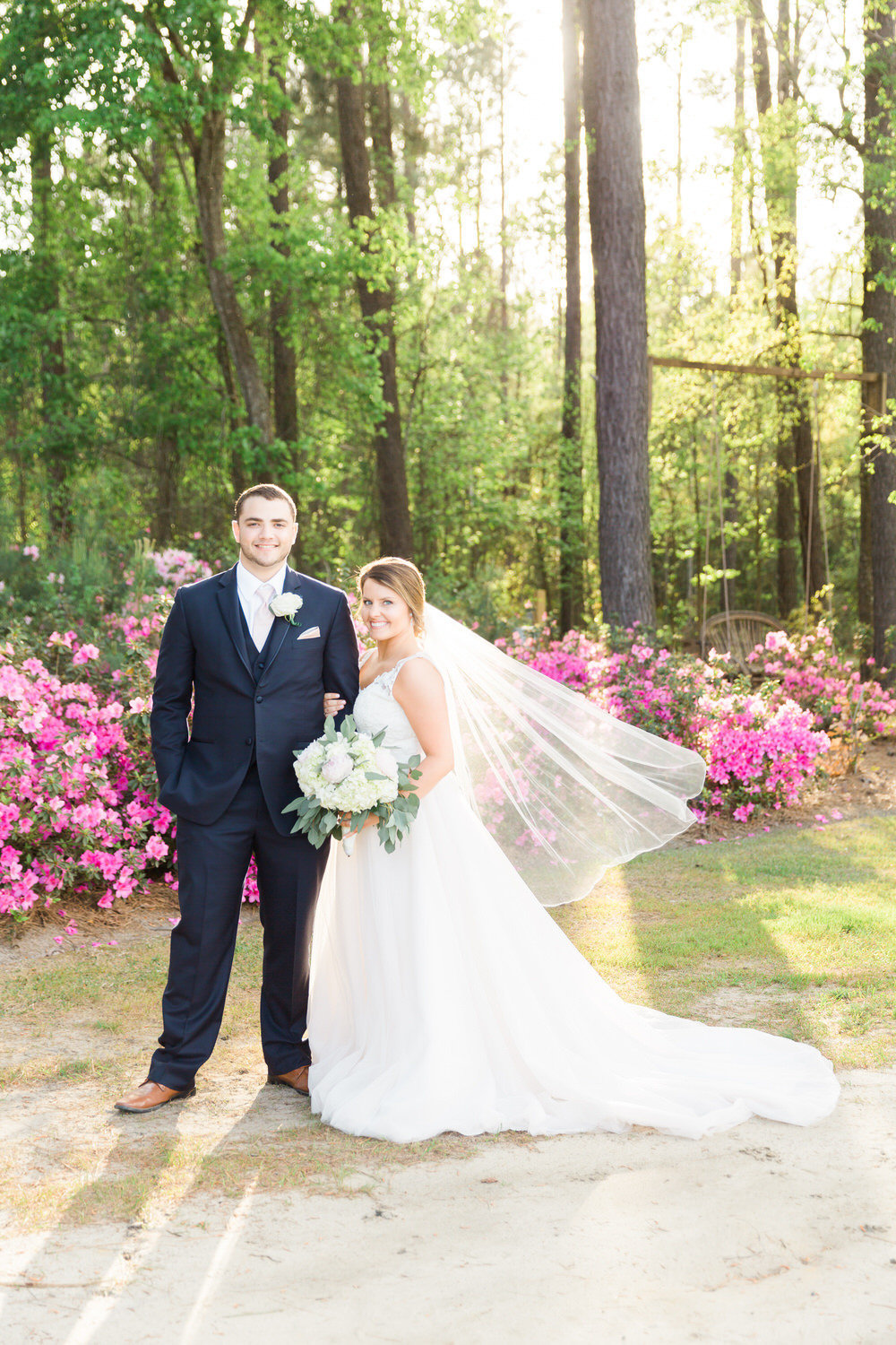 bride and groom posing with bouquet outdoors at sunset