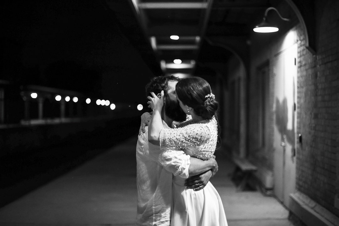 Bride and groom kiss along the train tracks at the Brewerie at Union Station