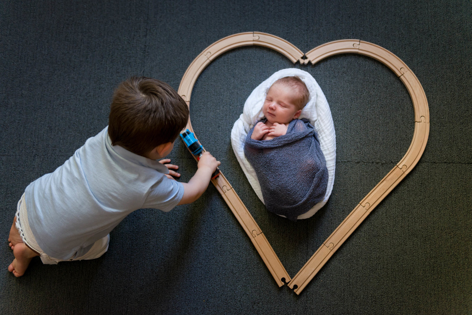 Sibling with train and newborn at home lifestyle session