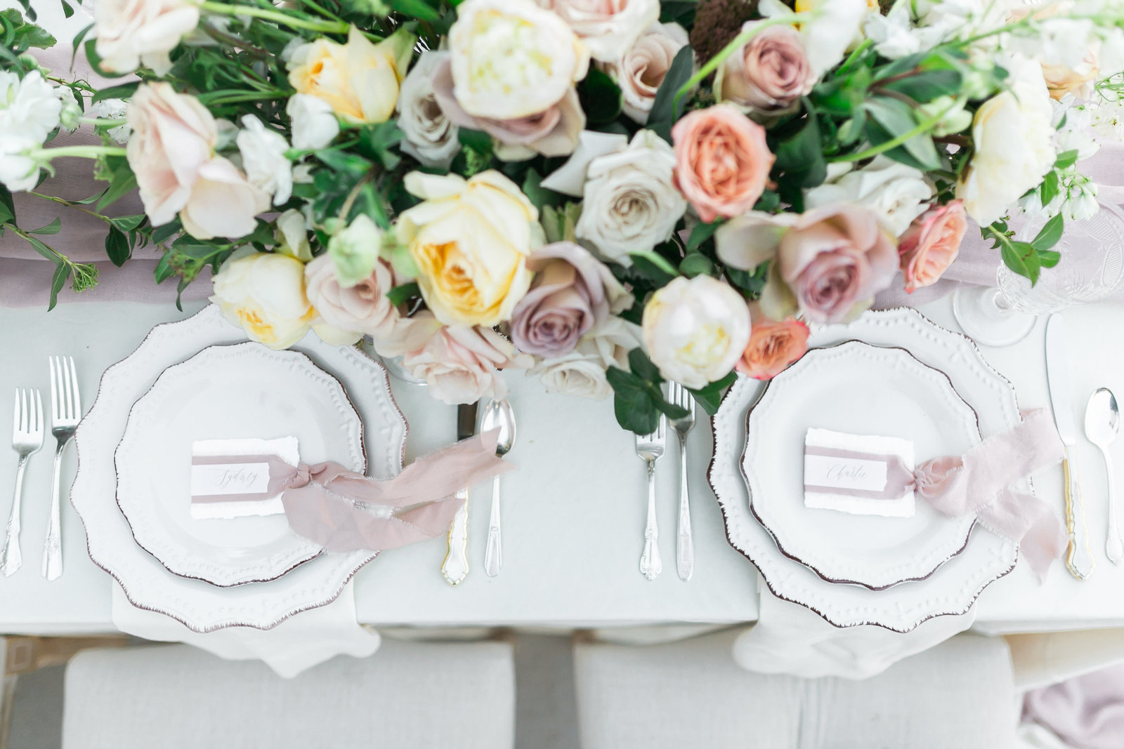 a photo of a tablescape with rustic plates, ribbon placecards, and a centerpiece filled with yellow, mauve, blush, and apricot colored roses