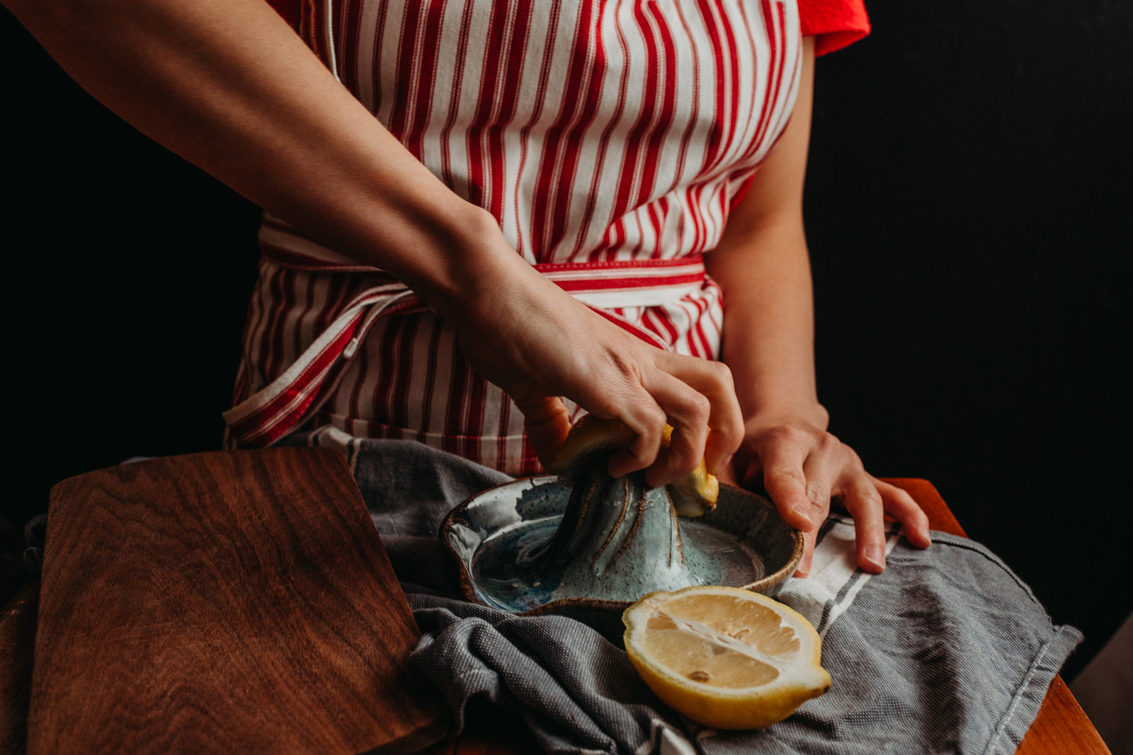 woman presses lemon onto juicer while wearing a red striped apron