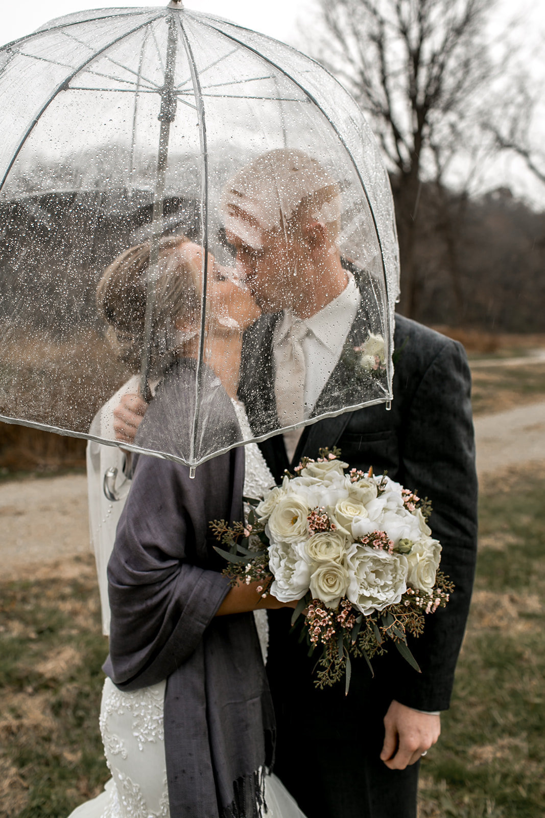 Des Moines Iowa wedding couple kissing together under an umbrella in the rain.
