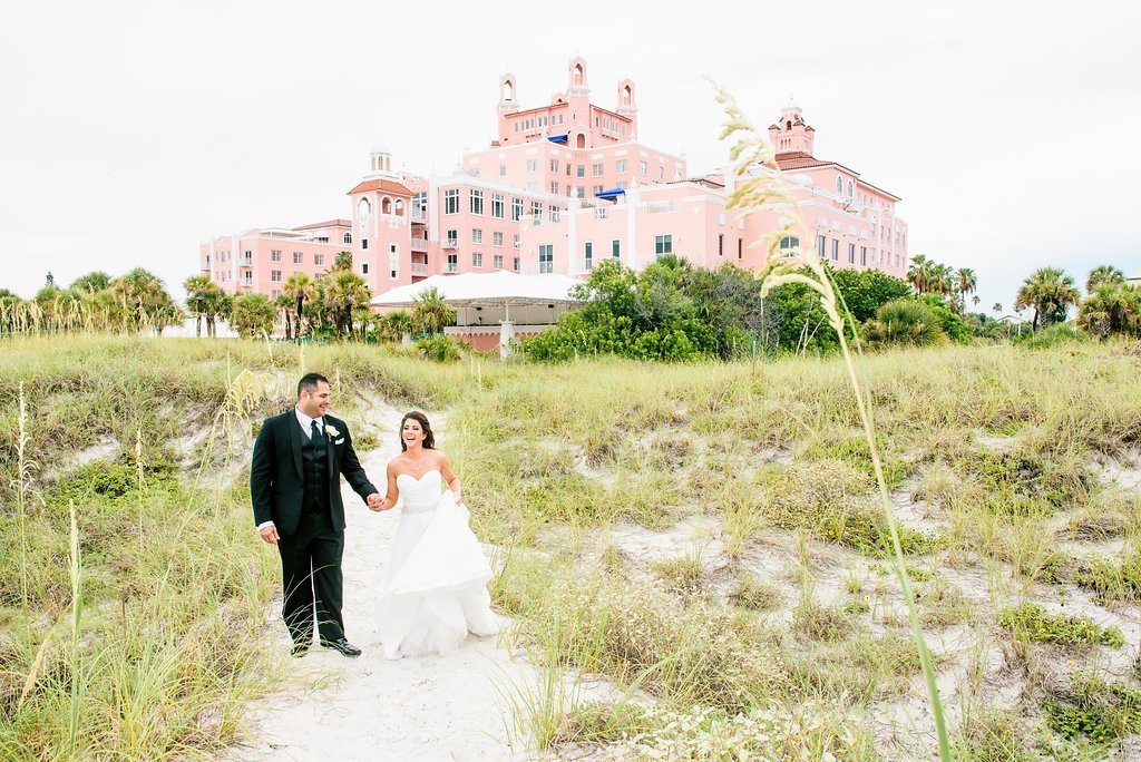 Bride and groom walking outside of resort on wedding day