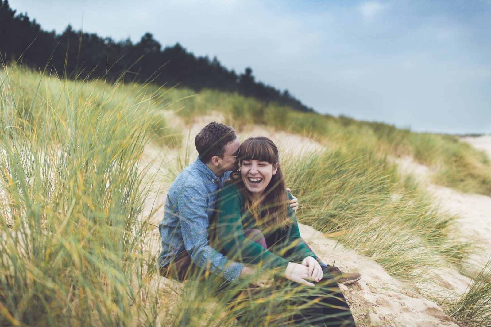 In the sand dunes at Wells-next-the-sea Norfolk we see a happy engaged couple laugh as they sit and talk.