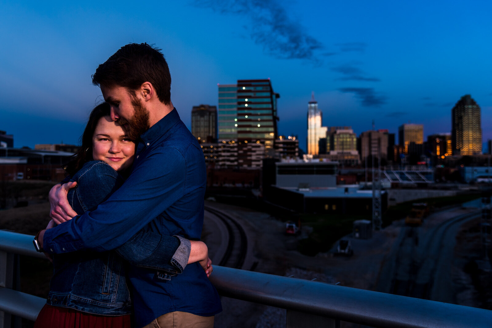 Couple embraces on Boylan Bridge overlooking the downtown Raleigh skyline
