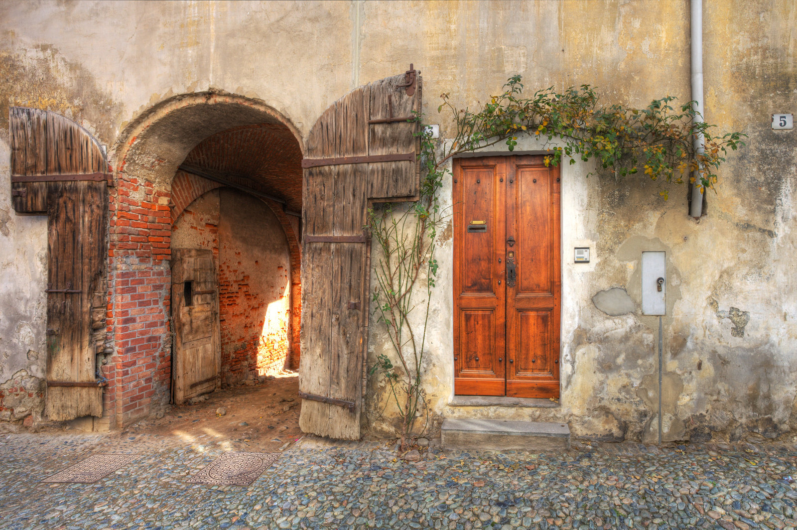 Wooden door and gate entrance to garage in old brick house in town of Saluzzo