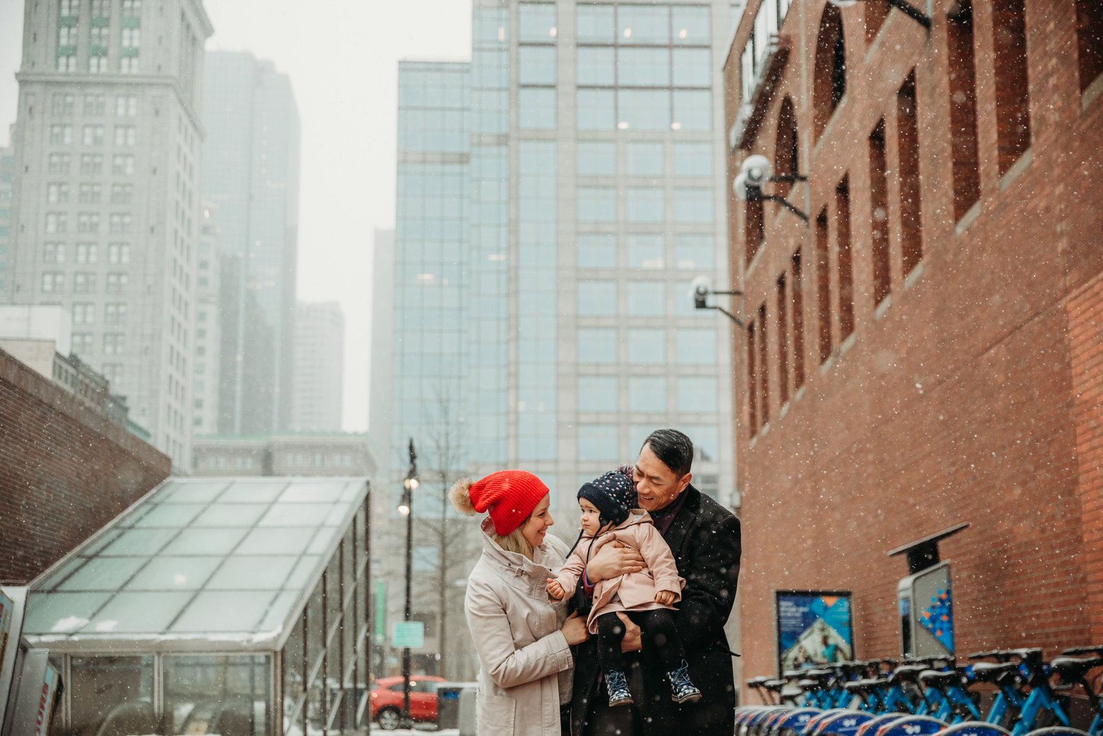 family in winter hats snuggle for winter snow session in boston