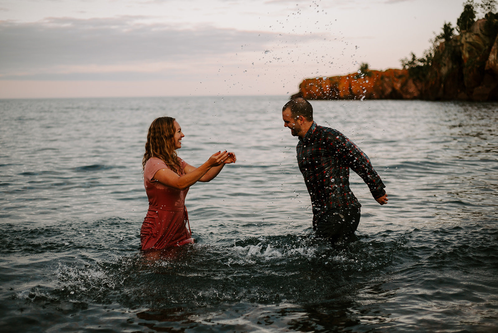 Couple splashing each other playing in the water at the North Shore in Minnesota during their engagement session