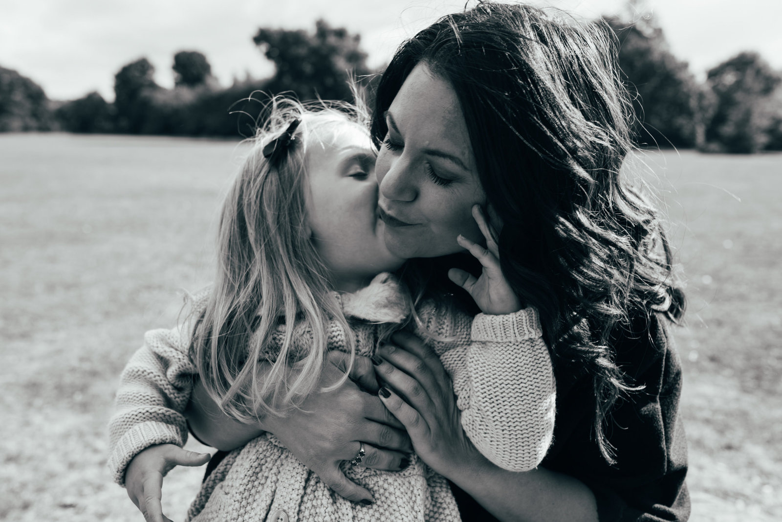 Black and white relaxed photograph of mum and daughter kissing in Suffolk Christchurch Park