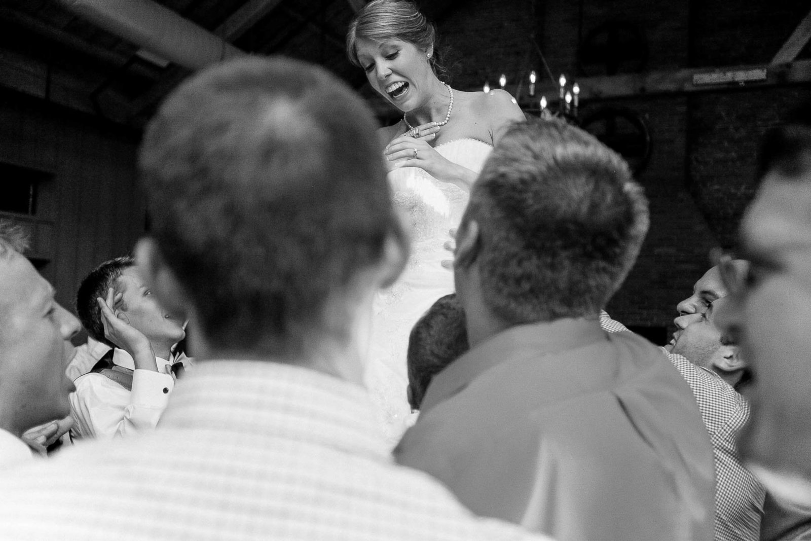 Bride is lifted by guests at reception, Cork Factory Hotel, Lancaster, Pennsylvania