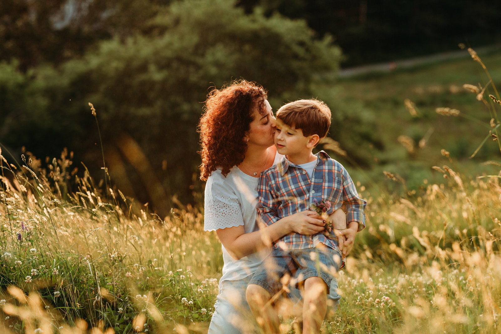 mom snuggles older son at sunset in field in southborough ma