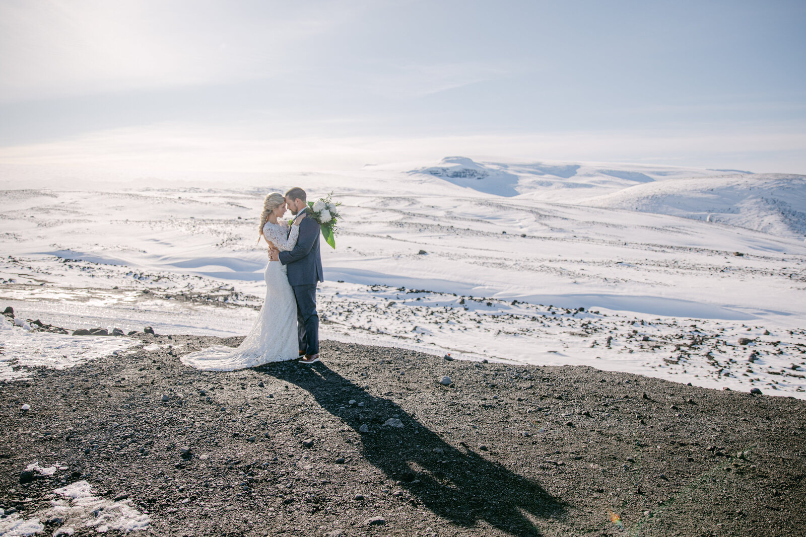 bride and groom face each other in iceland terrain