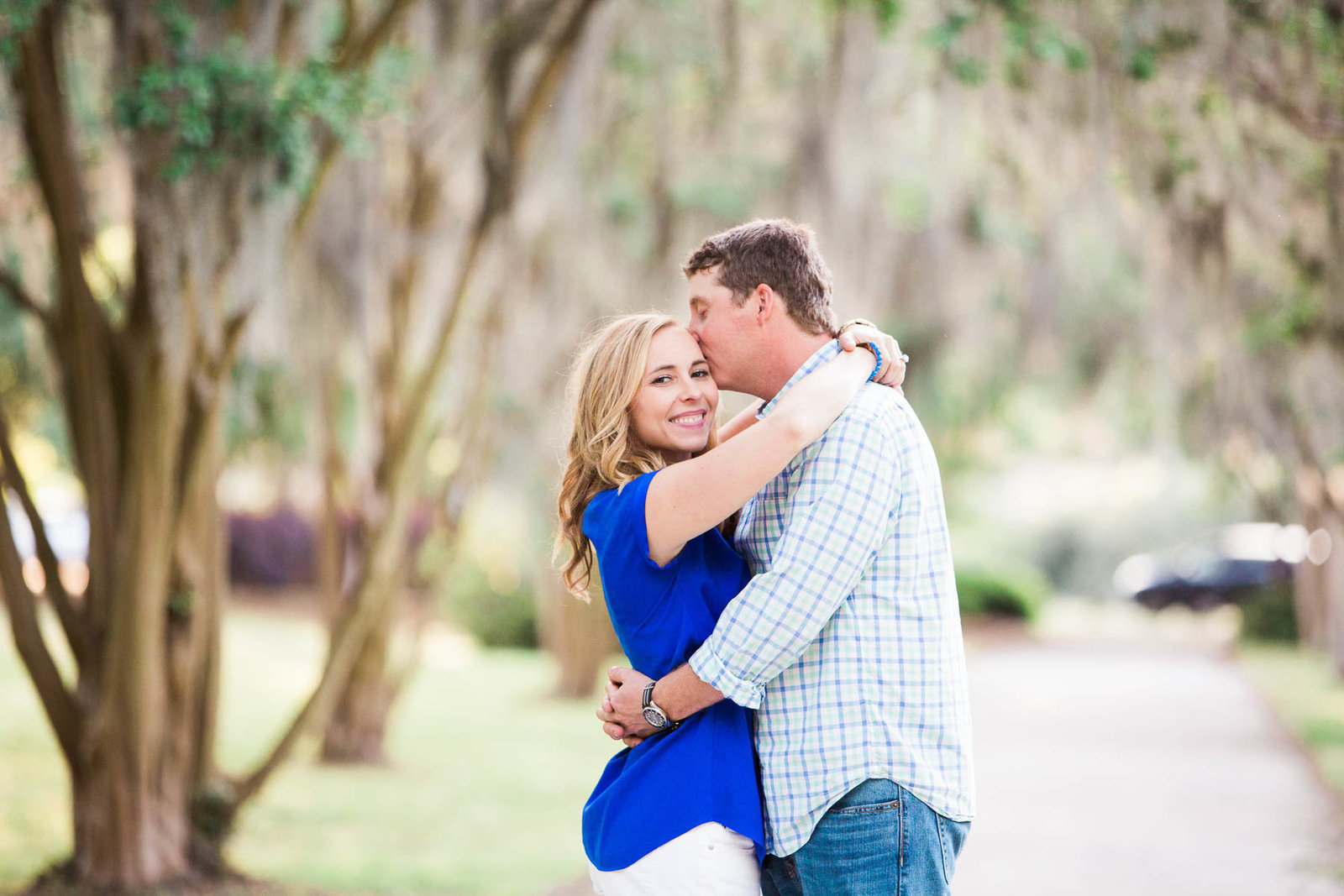 Engaged couple stand in pathway full of trees and spanish moss, Hampton Park, Charleston Engagement Photographer.