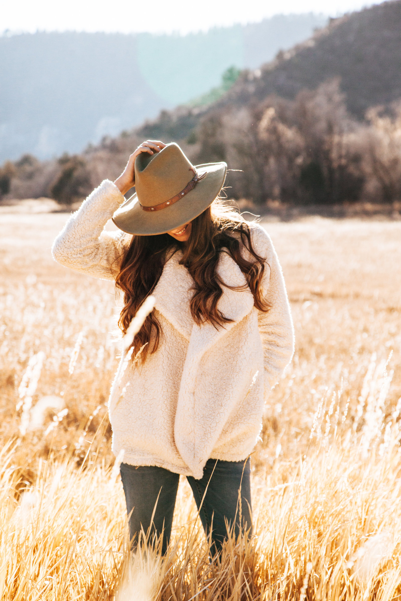 miling Woman in White Winter Jacket Wearing Brown Cowboy Hat Surrounded of Brown Grass Field