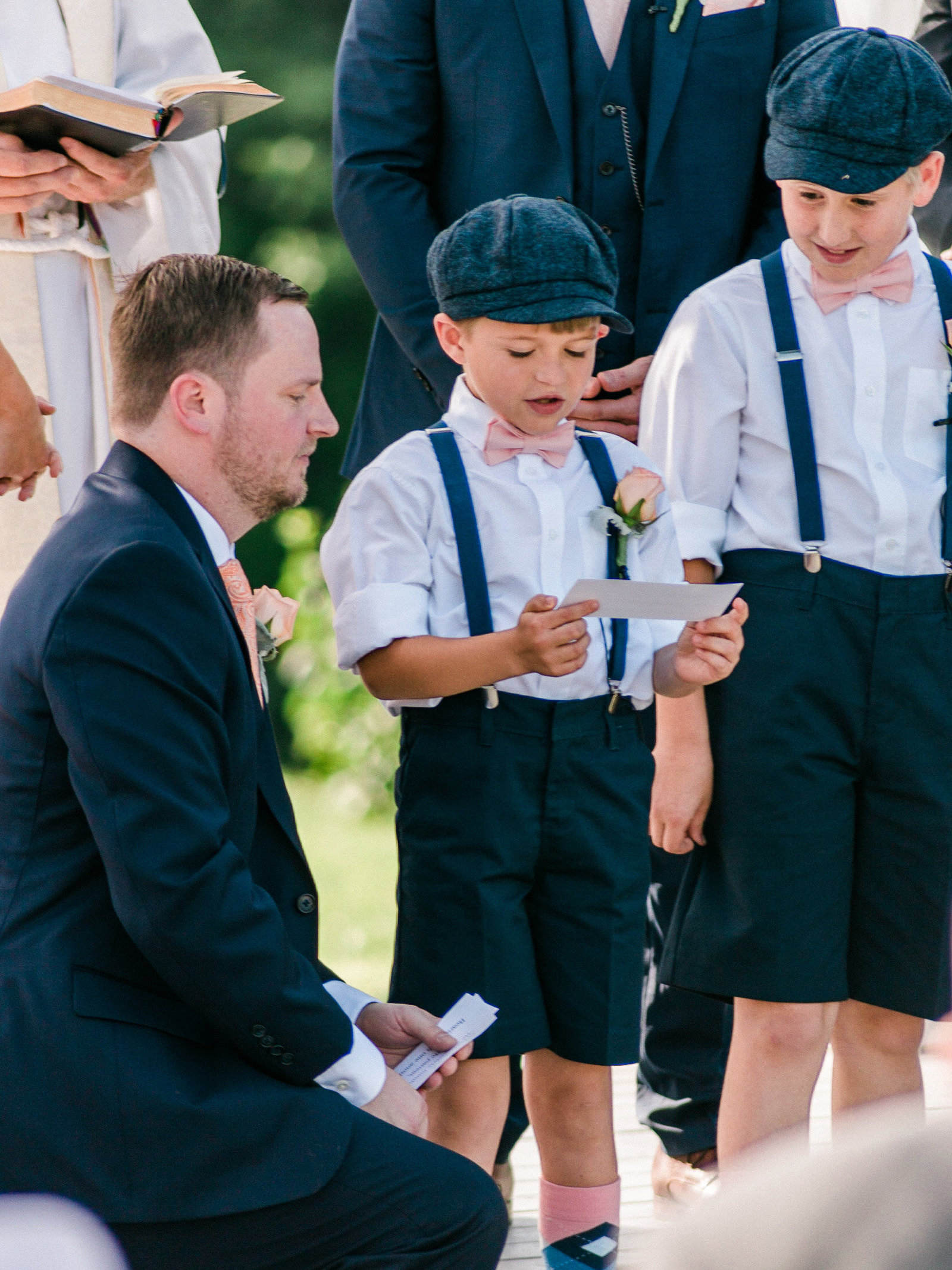 Pageboy in flat cap and suspenders reads aloud during the ceremony